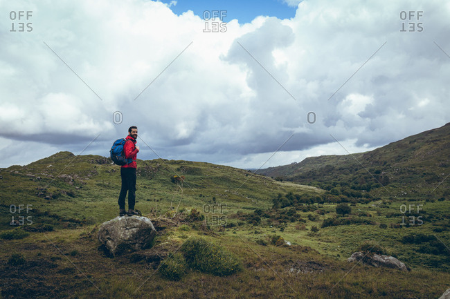 Male hiker with backpack looking around on the green countryside landscape