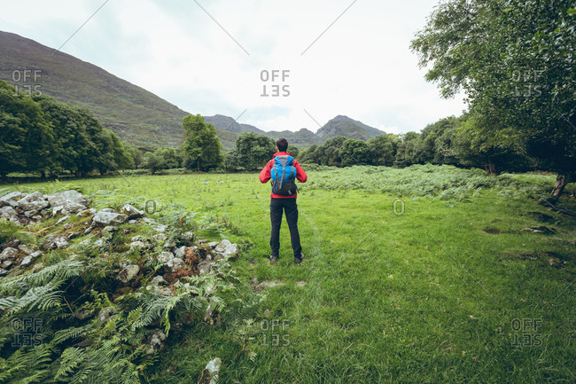 Rear view of male hiker looking at beautiful countryside landscape