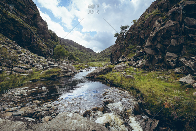 Calm stream flowing through mountains on countryside landscape