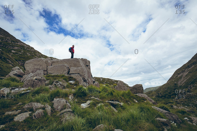 Male hiker standing on the rock on countryside landscape