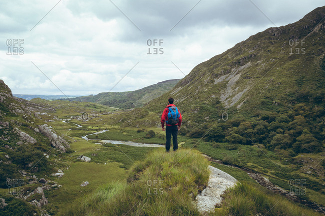 Rear view of male hiker standing on the countryside landscape