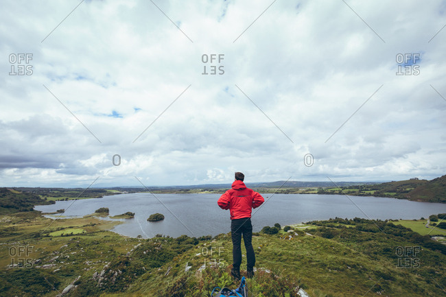 Rear view of male hiker standing near the lake on countryside landscape