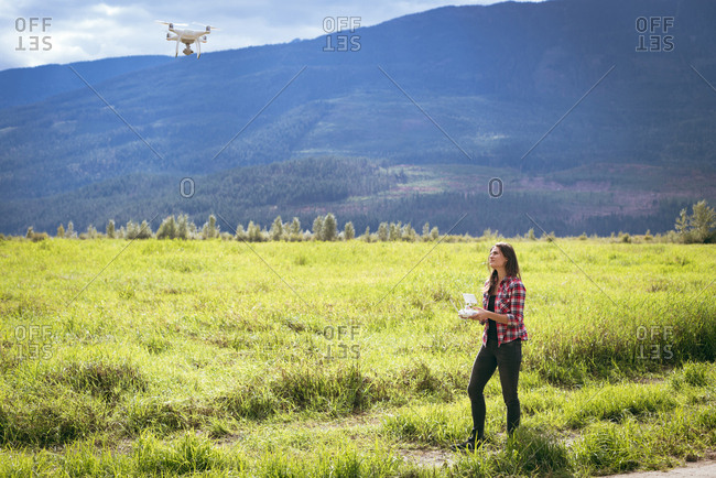 Woman operating drone using a remote control on the green mountains