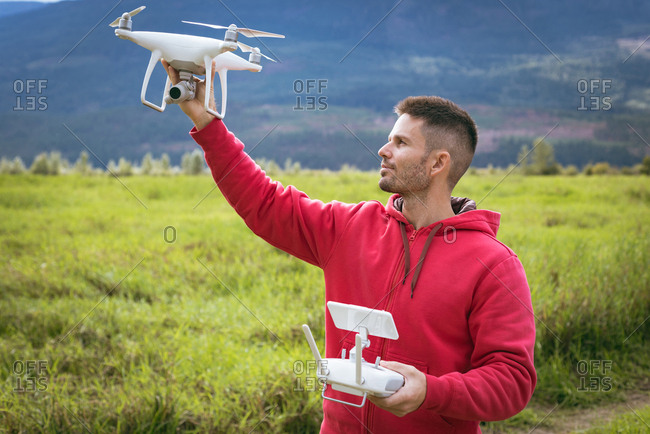 Man with a remote control holding drone while standing in grass