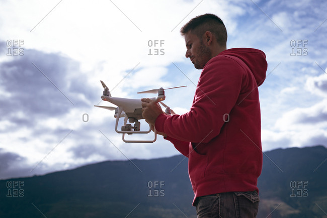 Man in red hoodie holding drone before take off
