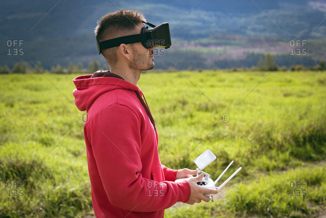 Man standing on a grass wearing virtual reality glasses and controlling drone