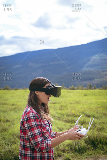 Woman in virtual reality glasses operating drone on a grass