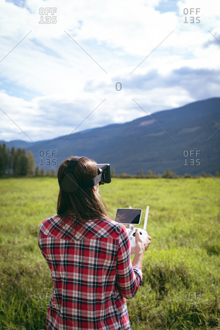 Woman in virtual reality glasses operating drone standing on a grass