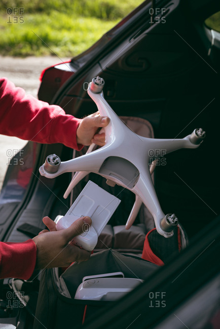 Two male hands holding a drone behind boot space