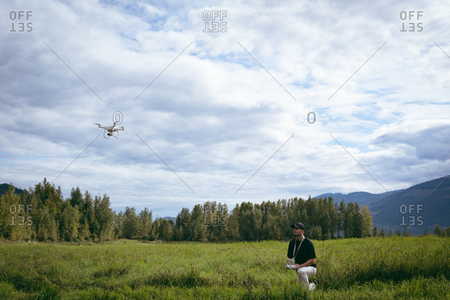 Man operating drone flying by remote control in nature