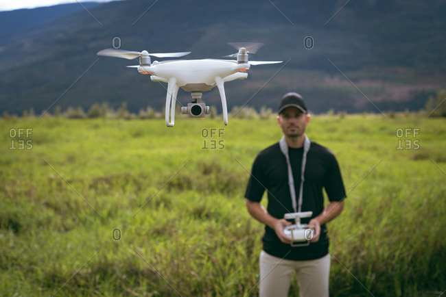 Close-up of drone in front of man with remote controller in his hands