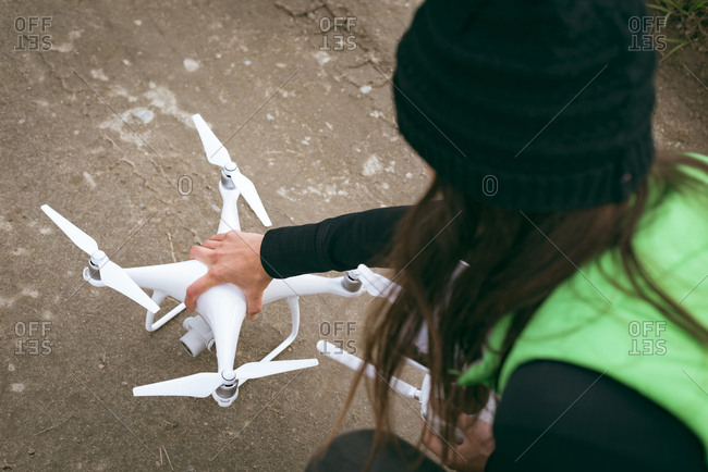 Woman placing drone on ground before take off