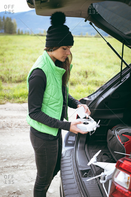 Close-up of woman removing gadget from car boot space