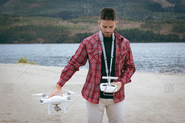 Man holding drone and remote control standing near the river