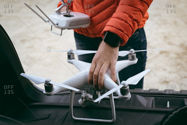 Close-up of man taking out drone from car boot space while holding remote control