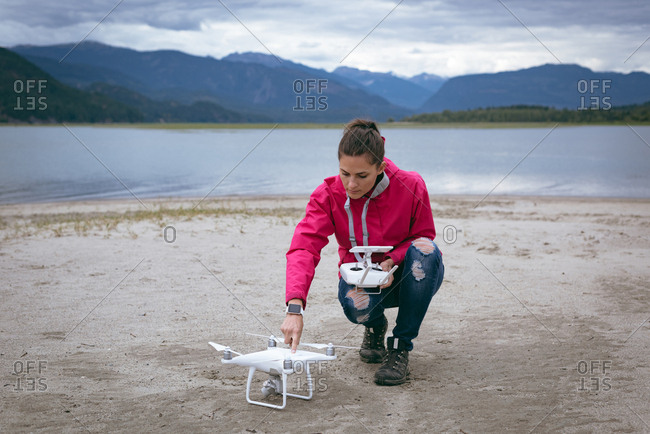 Woman checking drone before take off near the river