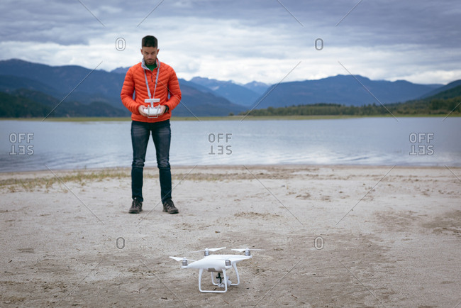 Remote control for the drone in the hands of man standing near river