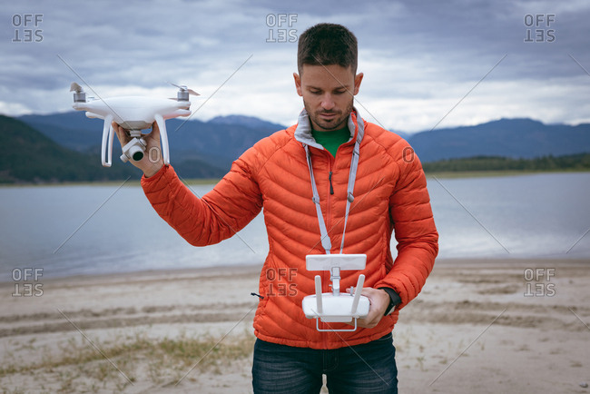 Close-up of man holding drone and remote control