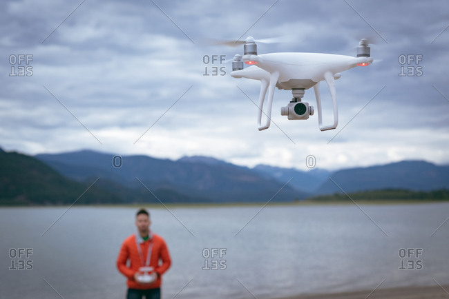 Man standing near river and operating drone flying by remote control