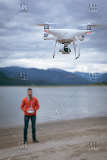 Close-up of man operating drone flying by remote control