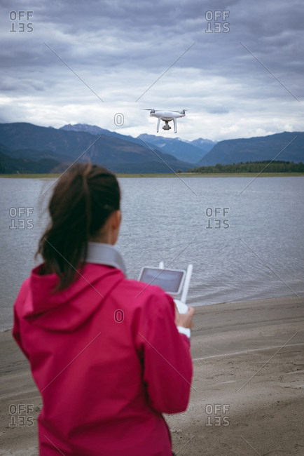 Close-up of woman operating drone flying by remote control