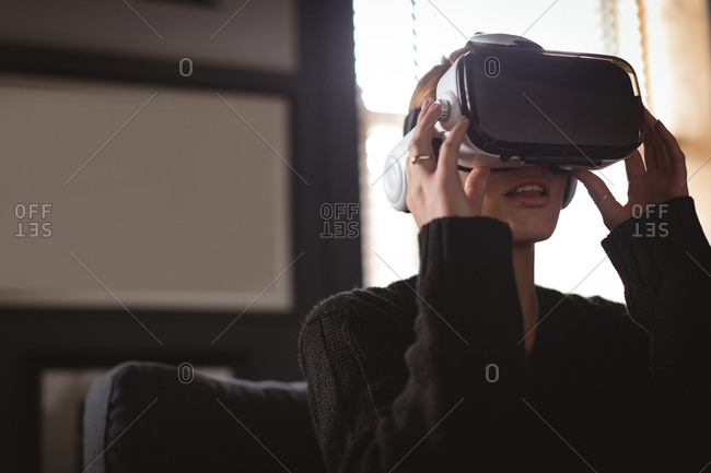 Woman using virtual reality headset in living room at home