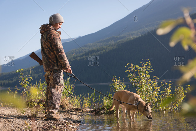 Hunter with his dog resting during the hunt on a sunny day