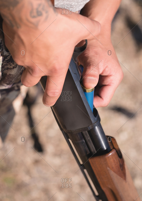 Close-up of hunter loading bullet into rifle