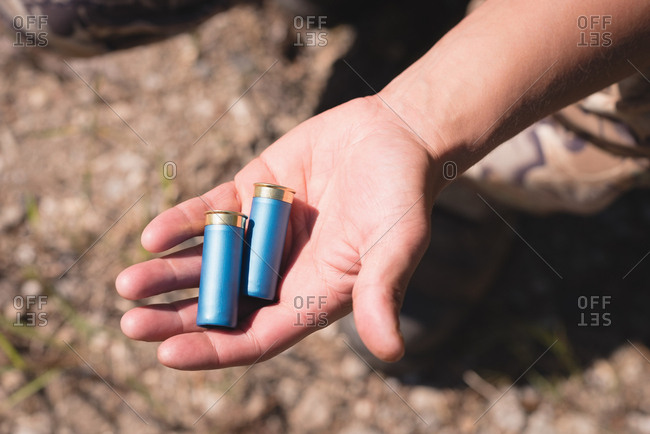 Close-up of hunter holding bullets in hand