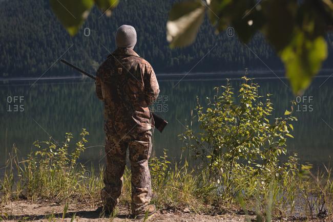 Rear view of hunter with shotgun standing near lake