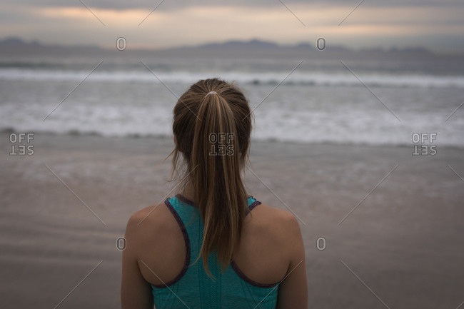 Rear view of woman in sports wear with ponytail standing at beachfront