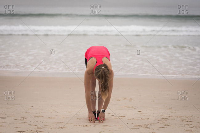 Sporty young woman bend down at the beach during dusk