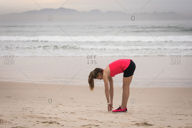 Side view of sporty young woman bend down at the beach