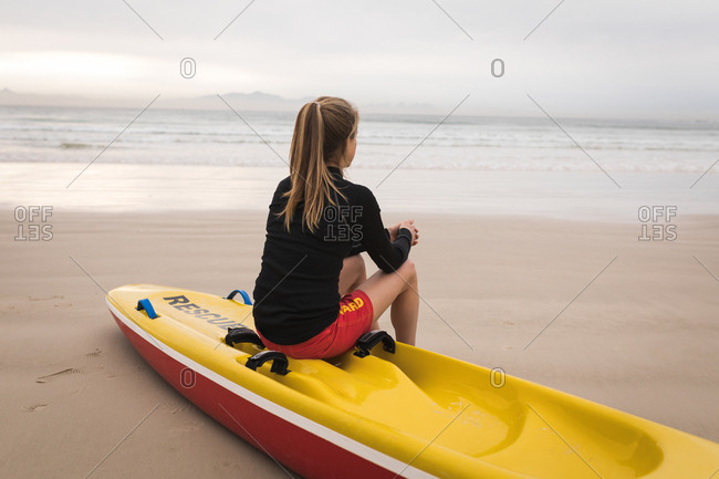 Female lifeguard sitting on rescue boat at beach during sunset