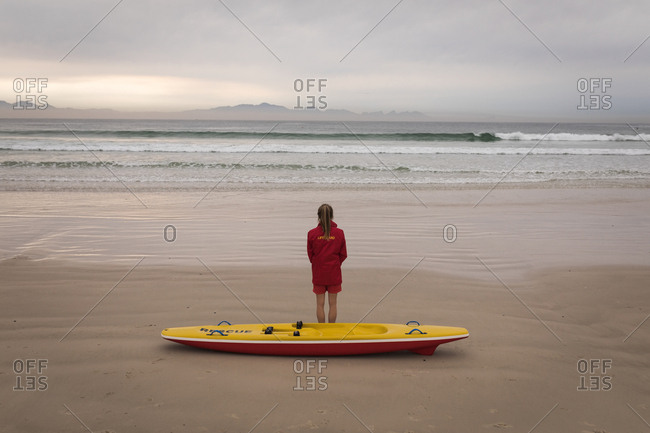 Rear view of female lifeguard standing on the beach with a rescue boat