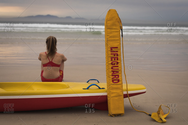 Close-up of female lifeguard sitting on the beach with a rescue boat and float