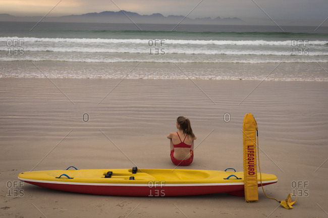 Rear view of female lifeguard sitting on the beach with a rescue boat and float