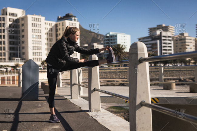 Woman performing stretching exercise on railings on a sunny day