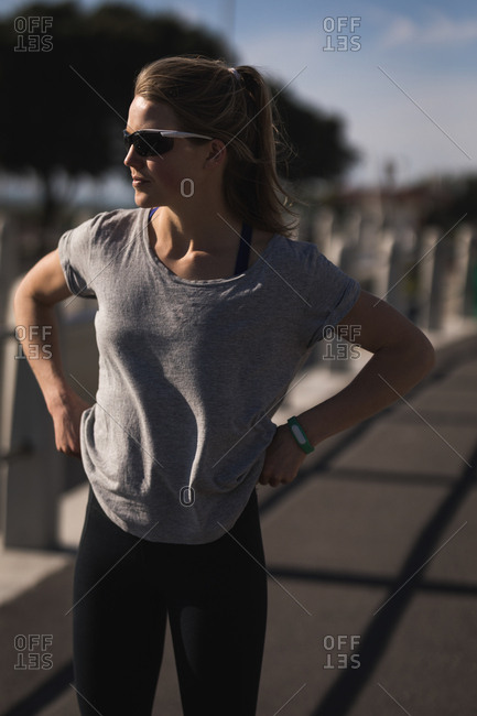 Close-up of Woman runner standing on road wearing sun glasses and fitness band