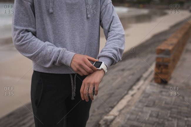 Close-up of athlete checking and adjusting watch