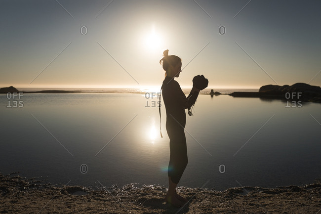 Woman standing near coast wearing swimming cap during sunset