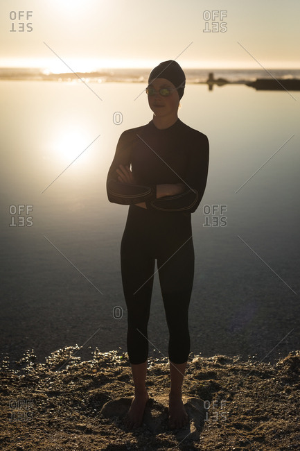 Woman in wetsuit standing near coast during sunset