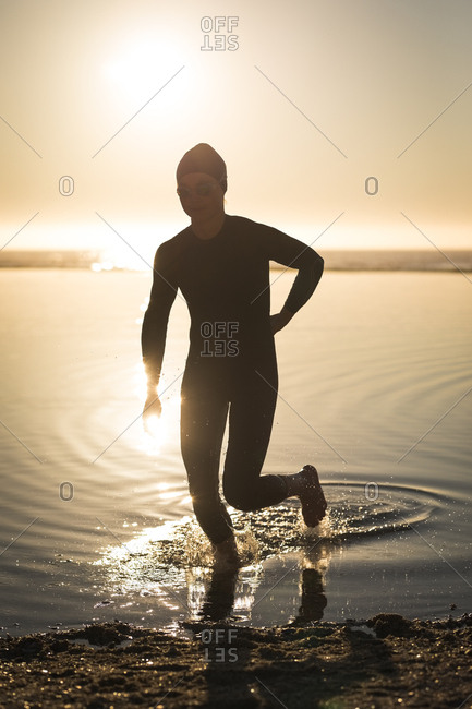 Woman in wetsuit running in shallow water during sunset