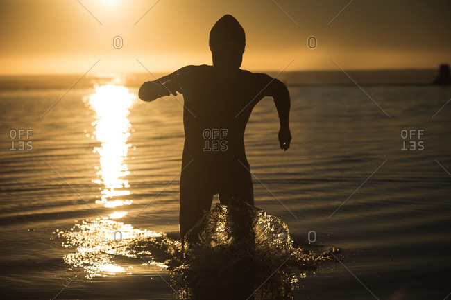Woman running in sea water during sunset