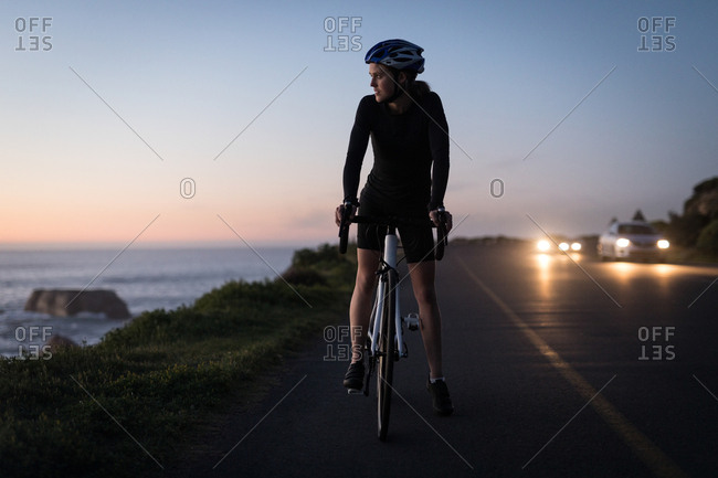 Woman on bicycle standing near coast during sunset