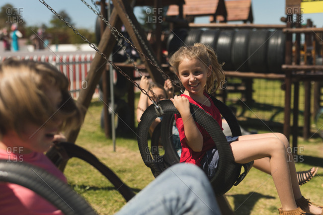 Children swinging on tire swing on a sunny day