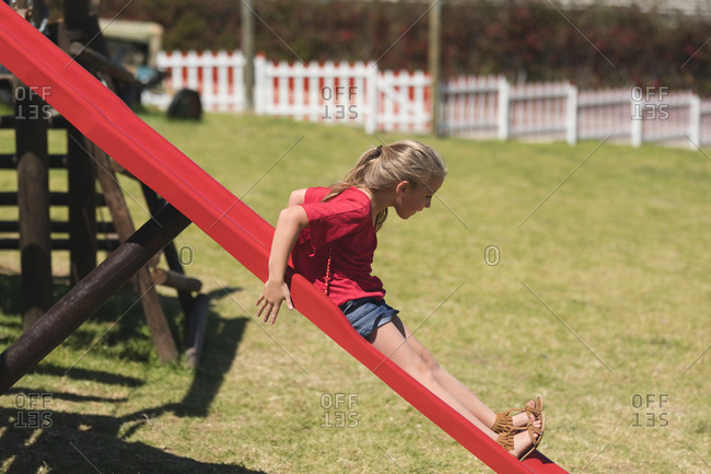Girl sliding on slide in playground on a sunny day