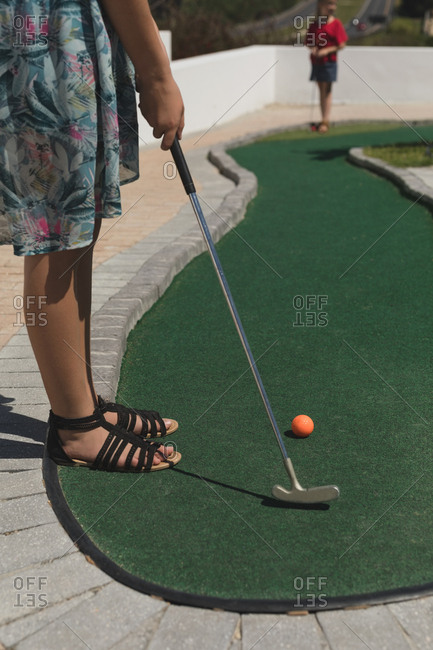 Girl playing golf in playground on a sunny day