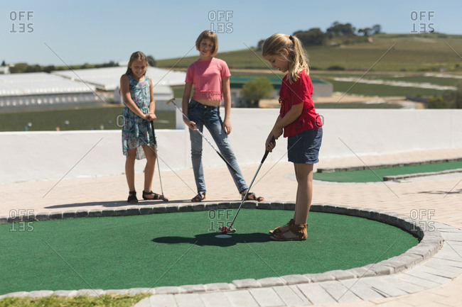 Girls playing golf in playground on a sunny day