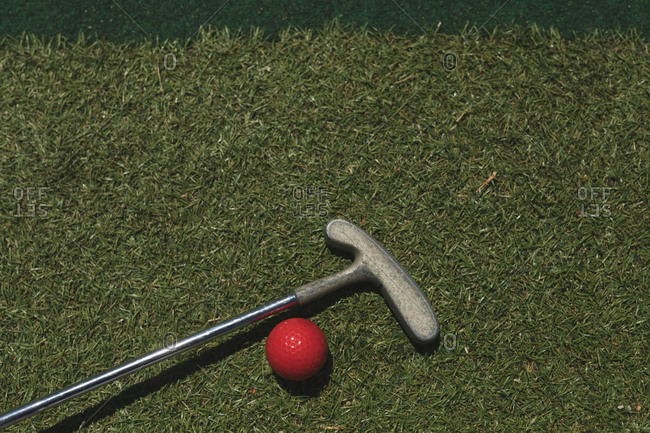 Golf ball with gold club on ground